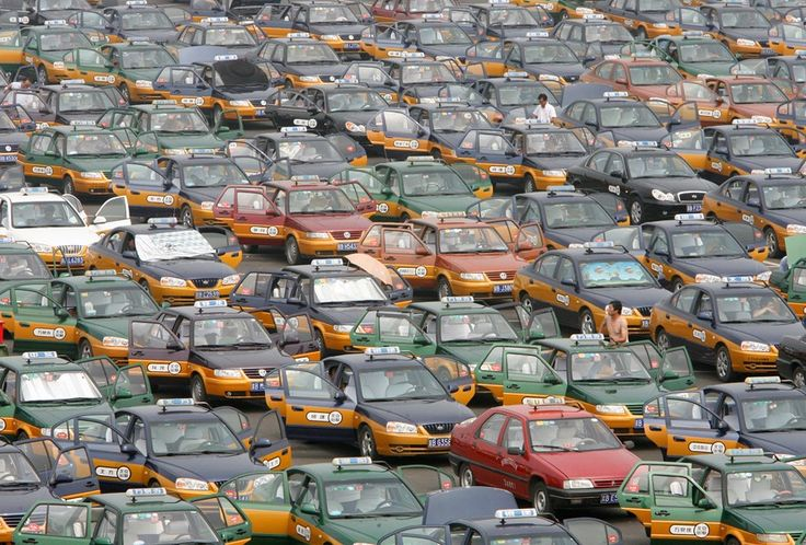 Taxi drivers line up in a parking lot while waiting for passengers at the new Beijing Capital International Airport.