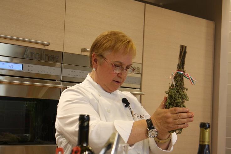 Lidia Bastianich seasoning some swordfish with dried oregano at our new cooking school classroom, La Scuola Grande!
