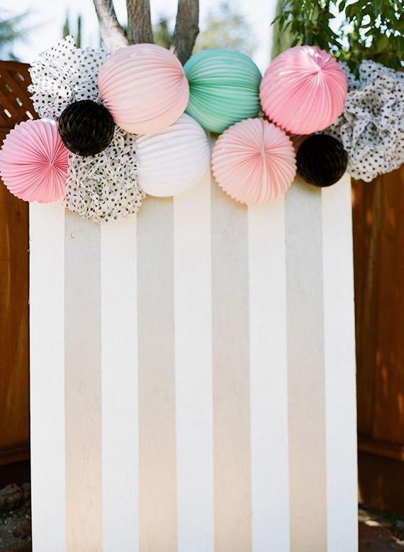 Card board, wrapping paper, & lanterns for a party backdrop!