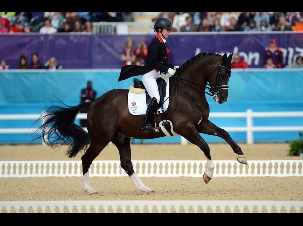 (Photo is by Neil Munns/EPA)    Charlotte Dujardin on Valegro at the 2012 London Olympic Games.  Dujardin and the GB team won gold in the dressage team event, which was impressive for obvious reasons, but I was doubly impressed that she wore a HELMET and not the traditional hat.  Hopefully more people will recognize that helmets won't affect your score and safety is more important than looking cool.