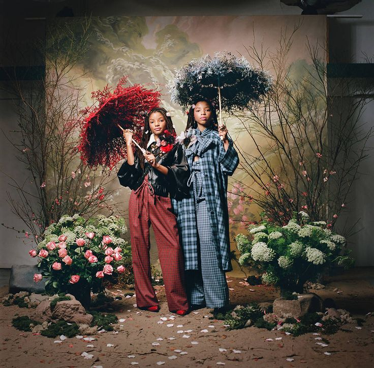 Look 14: Chloe x Halle from Rodarte Fall Winter 2018 Portrait Series  In a black leather jacket with bell sleeves and a shearling collar and a red plaid wool tailored tie waist pant (Halle)In a blue plaid wool bow neck cape coat, a blue plaid wool strapless bustier with bow detail, and a blue plaid wool tailored tie waist pant (Chloe)