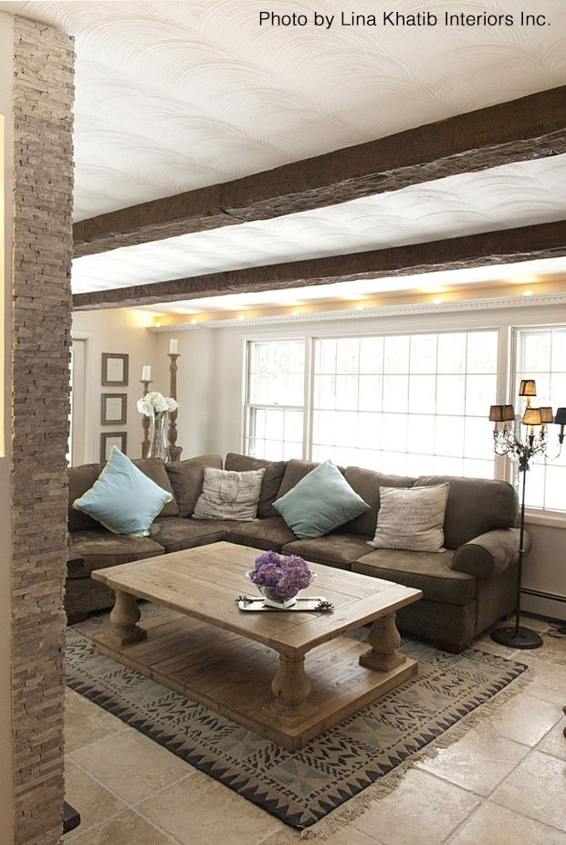 Southwestern pattern rug and wooden table are focal points to this remodeled living room. Ceiling beams add to that rustic appeal.