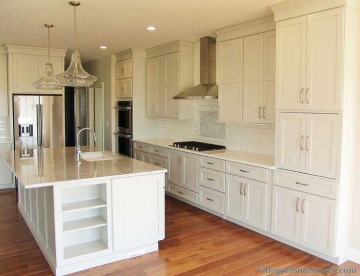 Transitional kitchen design with large island and custom layout tall pantry cabinets.    |    VilageHomeStores.com
