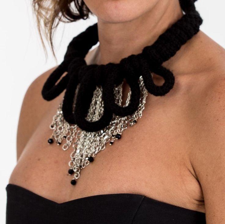 Collar elaborado artesanalmente a partir de una estructura metálica cubierta con un tubo tejido con hilo de lana de color negro empleando la técnica de crochet en punto bajo, cadenas color plata y piedras de cristal facetado.