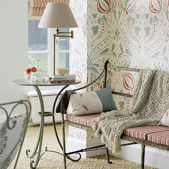 Garden room corner with patterned wallpaper, iron bench and table