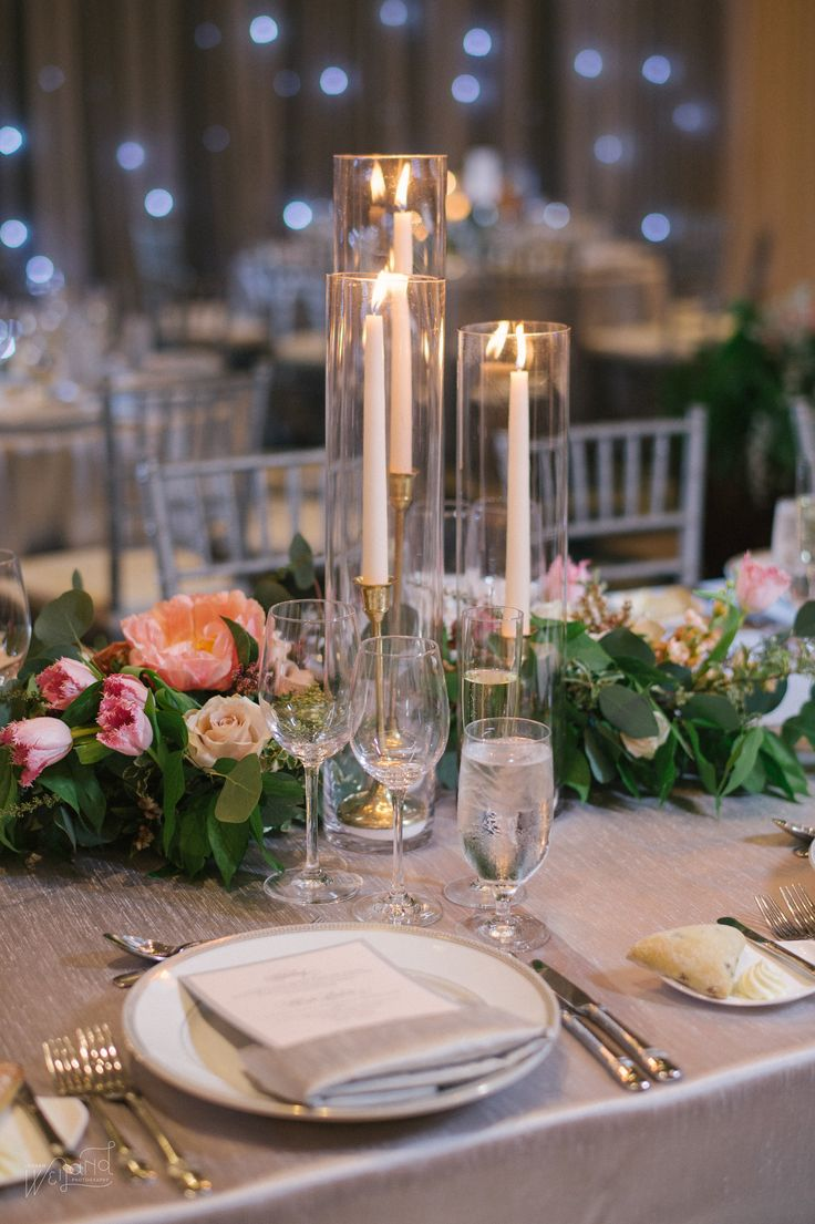 trio of taper candles in gold candlesticks is nestled in lush clusters of coral peonies, blush roses, ivory roses, pink tulips, peach stock, ivory spray roses, muted rust colored roses, variegated greenery, eucalyptus and greenery on silver table linens.