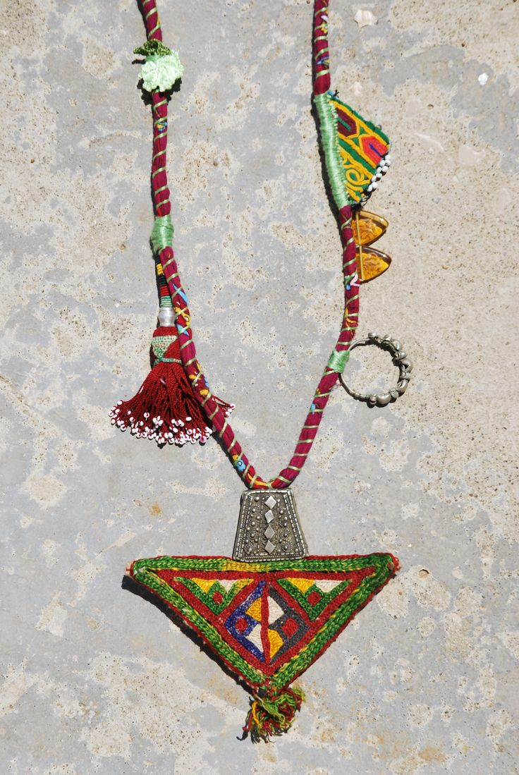 ETHNIC TREE: The base of this necklace is made with Turkish fabric, using a traditional tribal Turkish technique. The central triangle is Afghani and was used as part of traditional apparel. The tassel is Uzbek and comes from a wall hanging. The mixed silver is vintage Yemeni (17k). The rose is handmade in Turkey. Smaller triangles are Afghani glass beads and an Afghani amulet where women hid protective spiritual texts. The necklace is entirely handmade and is a unique piece…