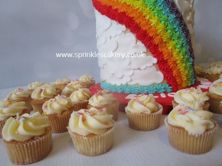 This rainbow cake for a 'Welcome To The World' party was complimented by some mini vanilla cupcakes.