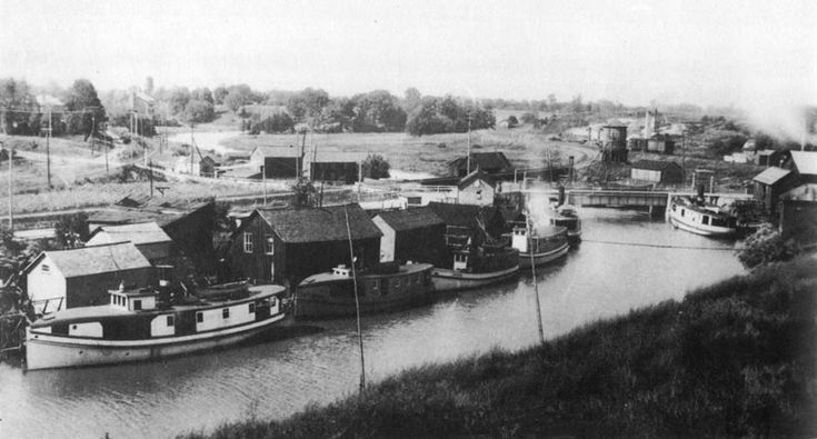 Fish tugs docked at their shanties with lift bridge and water tower in background. Early 1920's.