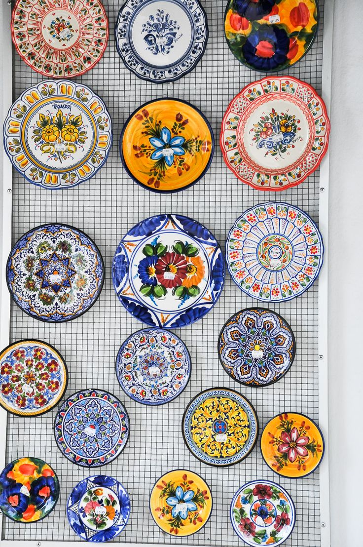 Traditional Spanish designs on plates for a colorful table presentation with paella, tapas and other Spanish dishes.