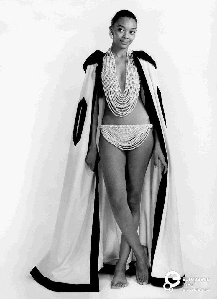 Majorca: costume bikini gioiello in fili di perle in due varianti. Modella 1: reggiseno con scollo ovale, allacciatura dietro al collo e slip a gonnellino finitura stondata. Modella 2: finiture a frange, slip a gonnellino.    Abbinato mantello in spugna di cotone nei colori del bianco e nero.