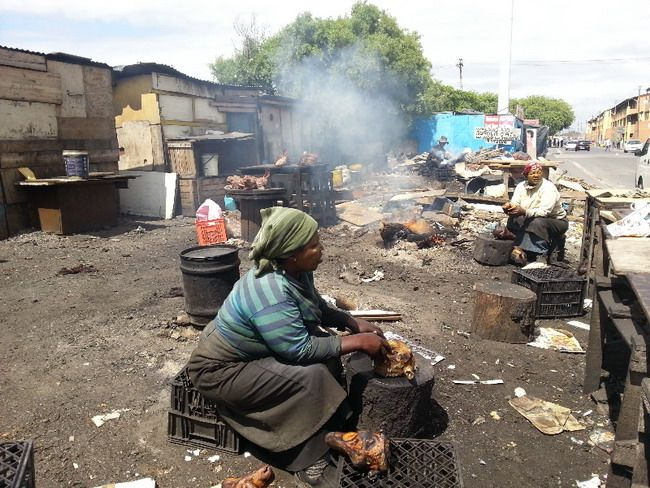 Khayelitsha - Local woman sit on the side of the road in the sun preparing a local delicacy known as a 'smiley',  (a sheep's head).