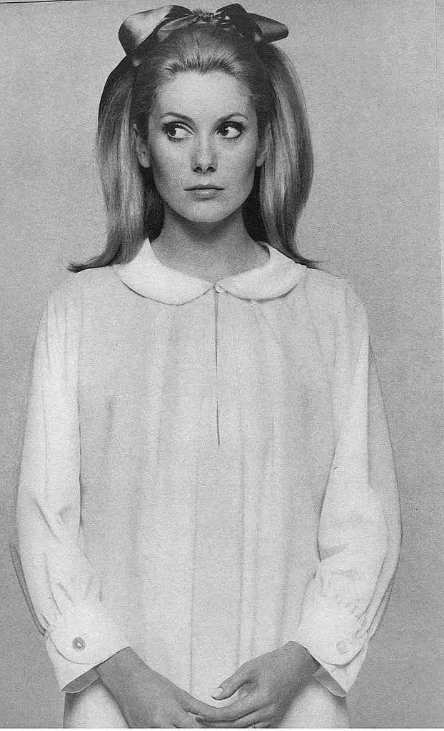 Catherine Deneuve is wearing a white crepe nightshirt with little round collar and cuffs by Sylvia Pedlar of Iris, photo by husband David Bailey for Vogue 1966.