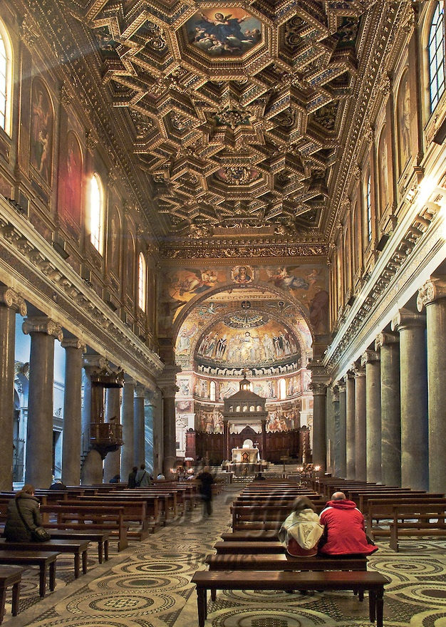 Santa Maria in Trastevere, interior, nave showing basilica form, carved and gilded coffered wooden ceiling (by Domenichino in 1617), and apse with mosaic by Pietro Cavallini, 1291, showing the Coronation of the Virgin.  The Ionic columns separating nave and side aisles are ancient Roman, from the Baths of Caracalla.  Daylight streams through the clerestory windows.  A couple sit on one of the benches contemplating the beautiful space.  Photograph made using available mixed light.