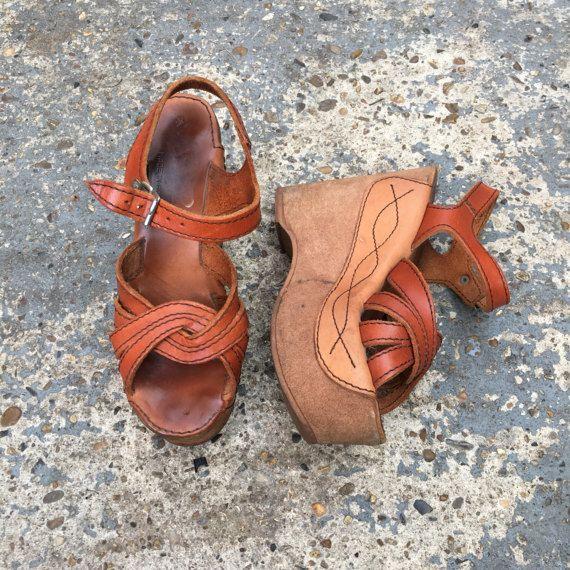Increíbles zapatos de plataforma de sandalia vintage original años 70.  Estilo de sandalias de cuero superior, con una plata hebilla de correa que va alrededor del tobillo. y Peep toes con cruzan de las correas en la parte delantera. Suela de cuero con viene por el lado con la costura. La cuña está cubierta de ante marrón.  Etiqueta: Stom Feris En Rumania tamaño 4  Medidas Longitud de calzado: 23cm altura del zapato en la parte posterior: 12.5/ 5 altura del zapato en la parte delantera: ...
