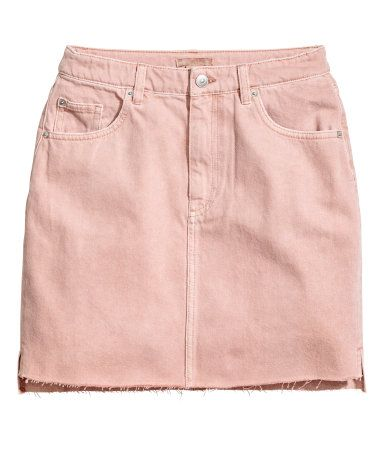 Light pink denim. Short 5-pocket skirt in washed denim. Zip fly with button, raw-edge hem with slits at sides, and slightly longer back section.