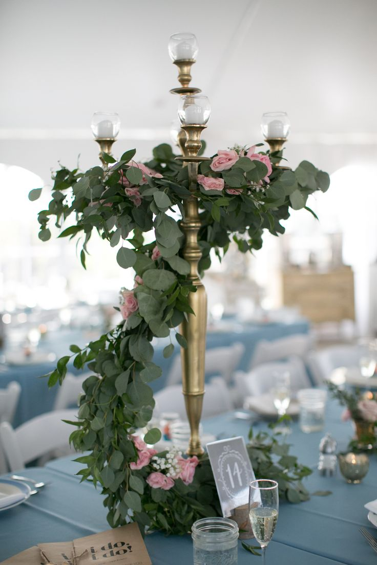 A seriously beautiful centerpiece by @floralwonders. We love the large gold candelabra and the eucalyptus around the centerpiece. The pink roses are such a lovely addition with the baby blue tablecloths. It's an elegant wedding tablescape that we love and very different than our traditional rustic weddings. Photography by Brittany Lynn Studios.