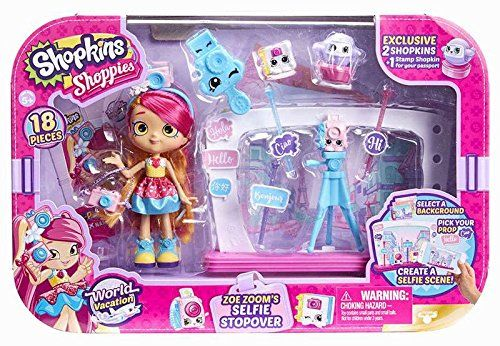 Shopkins - Zoe Zooms slfie Stopover - World Vacation  1 Shoppie, 2 Exclusive Shopkins, 1 Selfie Scene Frame, 3 Double Sided Scene Cards, 3 Prop Sticks, 6 Prop Quotes, 1 Camera Tripod, 1 Stamp Shopkin, 1 Doll Stand, 1 Passport, 1 Exclusive Hair Brush.  2 Exclusive Shopkins + 1 Stamp Shopkin for your passport  Get the Shopkins World! App, enter your shoppies passport code for VIP access & rewards!  18 pieces