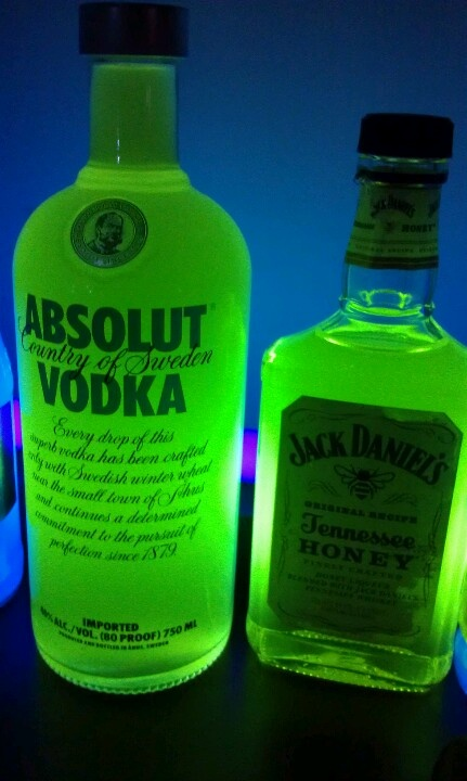 Cut open a highlighter and soak the fibrous material in water and pour the water into a glass bottle, place the bottles in front of a blacklight, enjoy!  Also works with laundry detergent for a blue glow, do 50% water 50% detergent