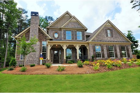 Four pillars frame the entry to this new home built with brick and stone accents. The Oakwood plan from D.R. Horton. The Heatherbrooke community. Acworth, Georgia