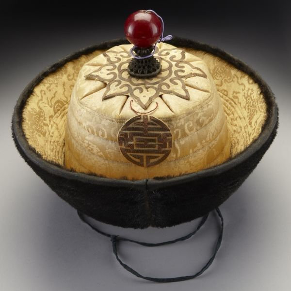 "Chinese Qing Dynasty prince's winter court hat having imperial yellow silk on the top, mink fur on the sides and a red amber bead on the top, circa 18th-19th centuries. Diamerter 6""H x 10""."