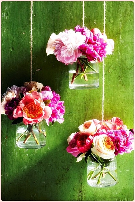 glazen potjes met bloemen aan touwtjes
