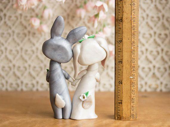 Ce one-of-a-kind, fait main, lapin gâteaux de mariage est orné de fleurs blanches et un noeud papillon noir. Je les sculpté à la main avec un mélange personnalisé, haut de gamme composé polymère qui a un éclat subtil et persillage. Leurs yeux sont des perles en cristal Swarovski et ils se tiennent juste sous 5-pouces de haut.  En plus de profiter de la vue sur le dessus de gâteaux de mariage, mes paires d'animaux sont souvent donnés comme cadeaux de fiançailles, mariage ou un anniversaire…