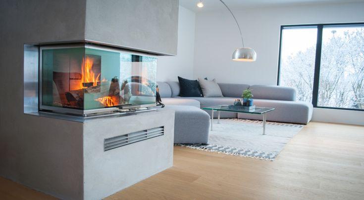 Peisen har tre glassvegger og kan nytes fra hele oppholdsrommet. #rais #design #interiordecor #fireplace
