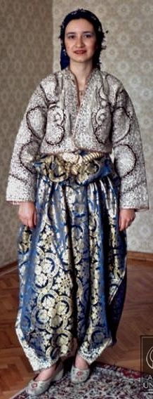 Traditional bridal/festive costume from the district of Sivrihisar (90 km east of Eskişehir).  The clothing style goes back to the early 20th century, and was then part of the culture of muslim emigrants from Macedonia. The costume was still in use in the late 1990s. The base of the dress are a heavily embroidered long-sleeves vest (called 'sarka') and very wide baggy trousers (called 'pesent', which can be embroidered too, or made of a brocaded fabric).