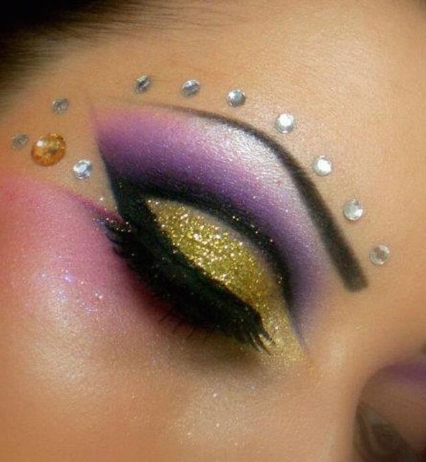 Dramatic crystal accented purple and gold smokey eye make-up.