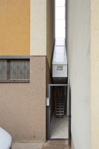 A porta de metal e o caminho de cascalho que conduzem à entrada da Casa Keret, em Varsóvia, Polônia.