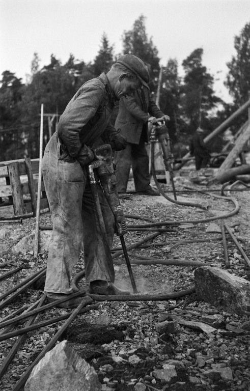 Rakennustyömaa todennäköisesti Meilahden sairaala-alueella. Työmiehiä poraamassa. 1950 -luku. Kuvaaja: Eino Heinonen Lähde: HKM (CC BY-ND 4.0).