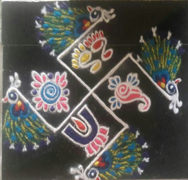 Beautiful rangoli with shaku,chakram, namam , laxmipadam & swasthik.....lovely peacocks by Jyothi mahajan kale.