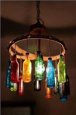 Rainbow Bottle Chandelier on repurposed vintage industrial frame. Wine bottles would make an interesting presentation in right room.