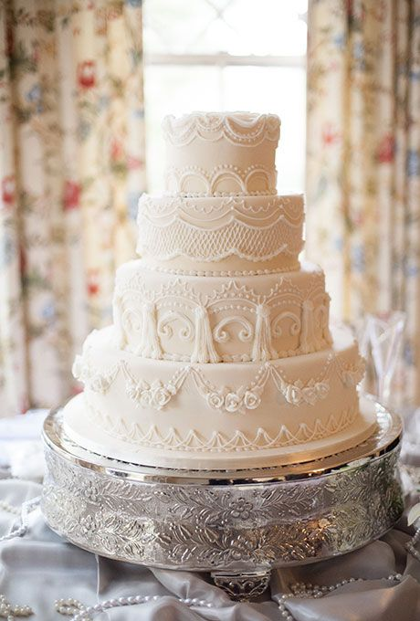 Brides.com: . A four-tiered white wedding cake with intricate piped details created by Dianna Tornow Cakes.