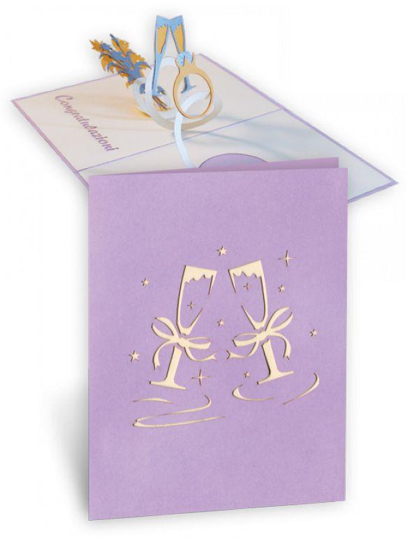 Un modo unico per festeggiare gli sposi! Anello con diamante, calici di bollicine e fuochi d'artificio: tutto racchiuso in un biglietto pop-up pronto a far esplodere i tuoi auguri ai futuri sposi!! Esterno colore lilla con due calici spumeggian