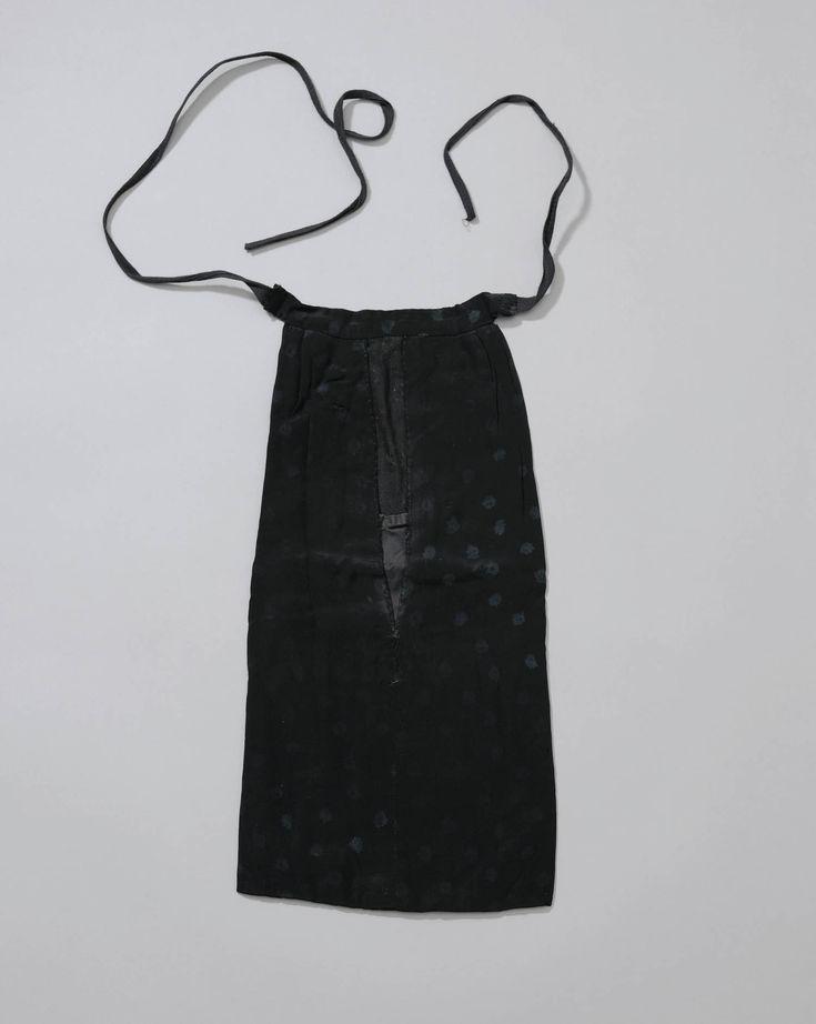 Zijzak van zwarte gedessineerde zijde. Zakken waren vroeger niet gebruikelijk in vrouwenkleding. Vanaf de 17de eeuw kwamen losse zijzakken of dijzakken in gebruik. Ze werden aan een bandje om taille gedragen, onder de bovenste rok. Via een split in deze rok was de zijzak bereikbaar. In de streekdrachten bleven deze zijzakken tot ver in de 20ste eeuw vrij gebruikelijk. Het model van een zijzak is een langwerpige zak met een opening in het midden.  #Cadzand
