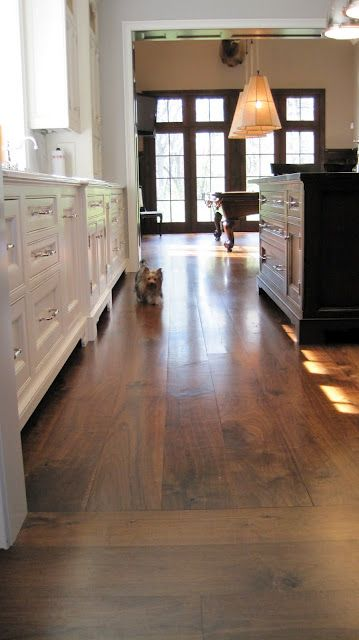 wide plank flooring + white cabinets + black island