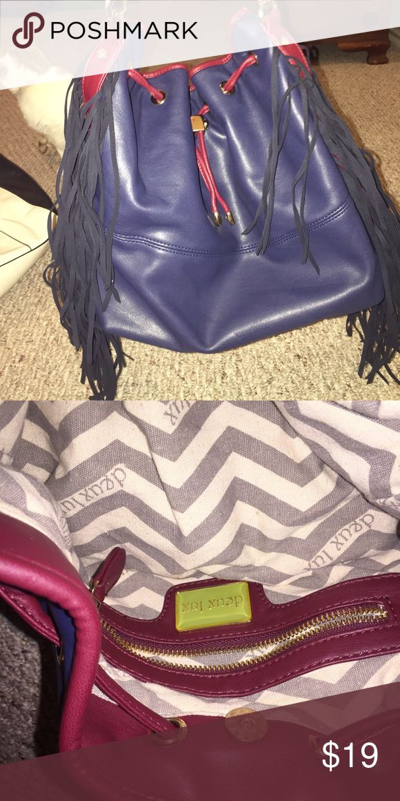 Deux Lux handbag I got this at a Nordstrom outlet. It's Deux Lux brand. Pic looks purple but it's actually a navy blue with burgundy detailing. The fringe matches the blue on purse perfectly but again pic makes it look like it does not. Gold accents and purse can be tightened or left loose at top. The purse is faux leather with faux suede fringe. It's very cute and in flawless condition. Only carried a few days. Deux Lux Bags Shoulder Bags