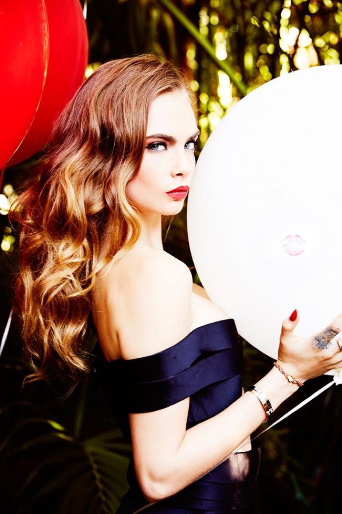 Captured with balloons, Cara Delevingne models her hair in blonde waves with a pop of red lip color