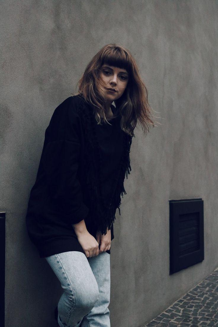 Uma mistura de poesia e moda. Look de inverno com pegada folk, casaco de tricot, calça mom jeans vintage, bota marrom e moletom preto com franjas.