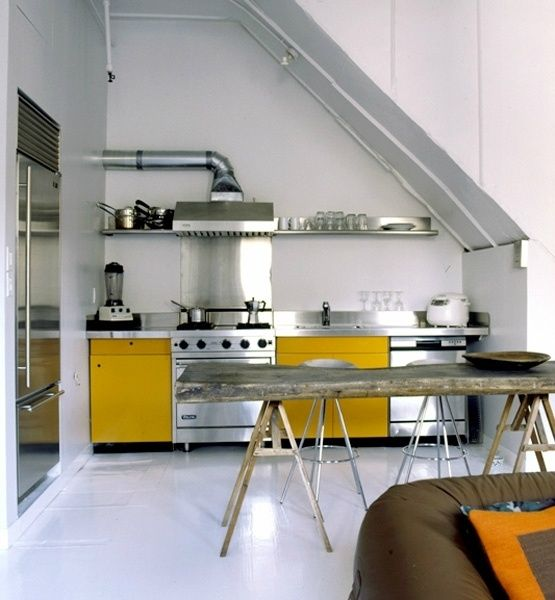 A compact kitchen tucked under a stairwell in the Broome Street loft project by Loading Dock 5 Architecture in New York.
