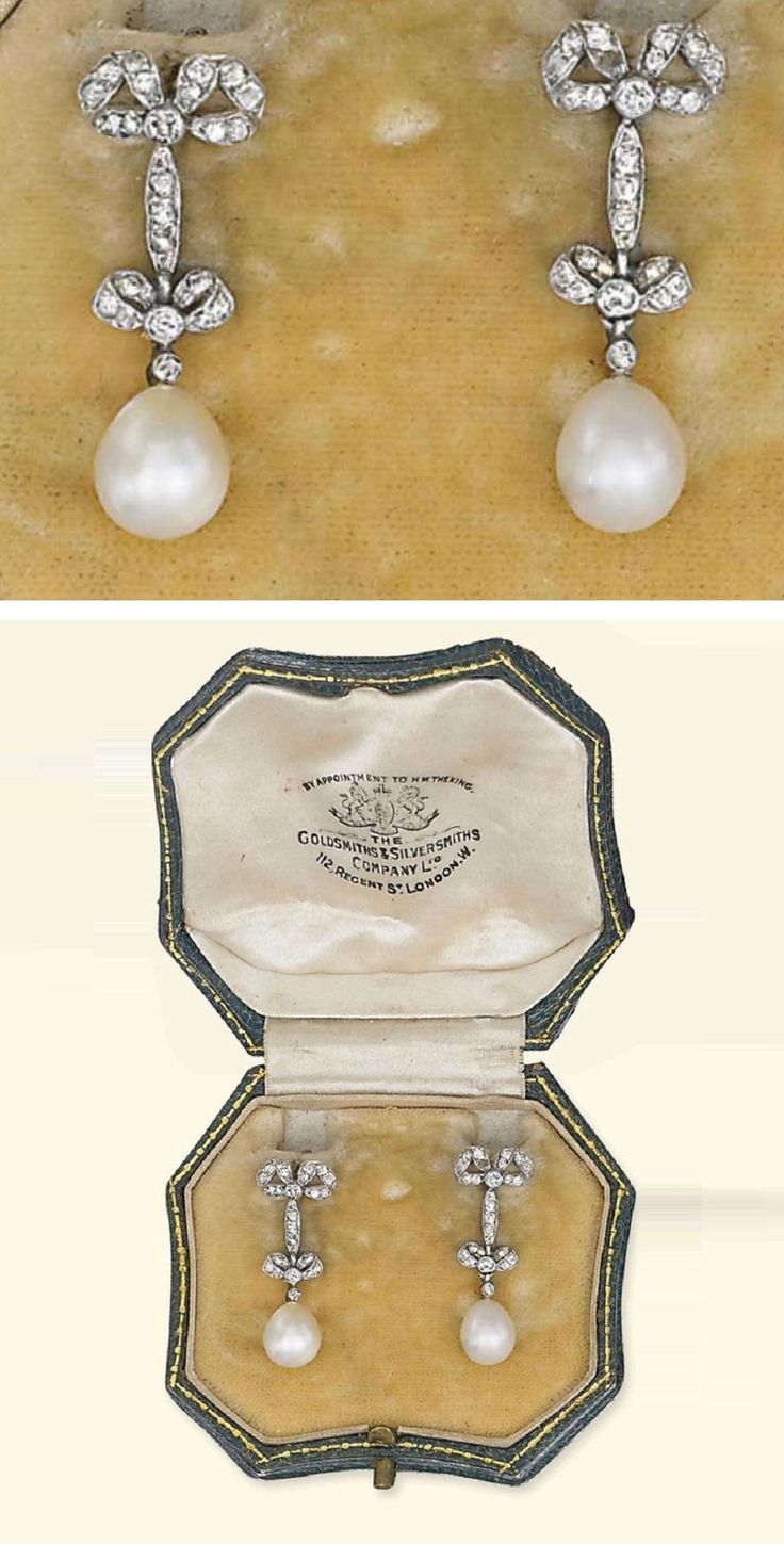 A PAIR OF BELLE EPOQUE NATURAL PEARL AND DIAMOND EAR PENDANTS, CIRCA 1910. Each suspending a drop-shaped natural pearl measuring 6.5mm and 6.3mm x 7.0-8.0mm to the diamond surmount of ribbon design, mounted in platinum, 2.5cm long, in green leather case by the Goldsmiths & Silversmiths Company Ltd.