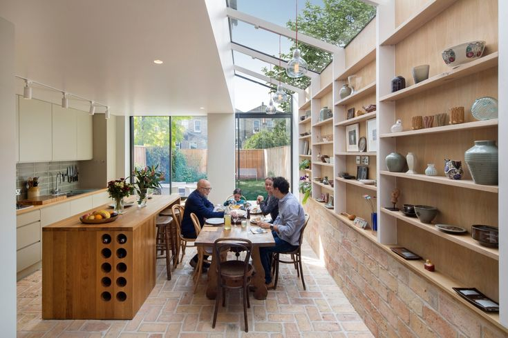 Kitchen with reclaimed brick floor and oak kitchen island with built-in wine bottle storage by Neil Dusheiko Architects in London