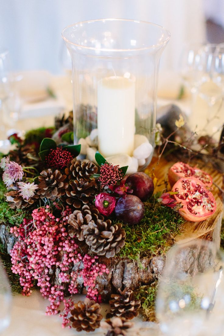 Autumn / Winter Table Centre piece on tree stumps with berries, pine cones & hurricane vase & candle - Image by Camilla Arnhold - Autumn wedding at Sopley Mill in Hampshire with a berry pink and grey colour scheme and a silver gown by Charlie Brear