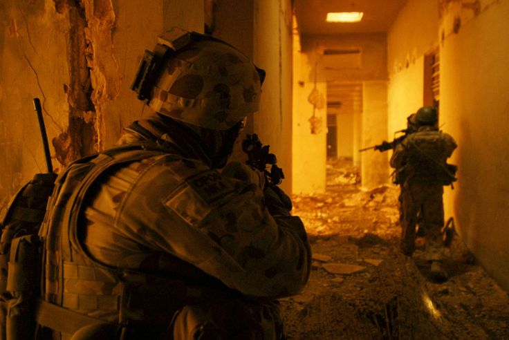 An infantryman of Australian Defence Force Combat Team Waler covers his mates while they progress down a rubble-strewn hallway of the Al Salman jail. [3000x2008]