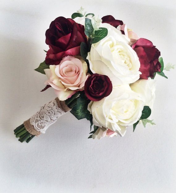 Silk Wedding Bouquet in the on trend Marsala colour. Made with silk roses in Ivory and Marsala/burgundy and greenery, finished with a burlap and lace wrap. This bouquet has a wild flower feel, they look so real, they are made with the highest quality silk flowers. These flowers