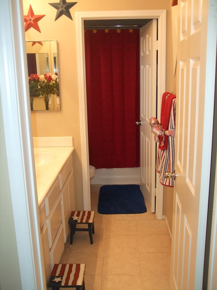 I totally re-decorated my kids bathroom into an Americana bathroom. I LOVE IT!!! I really do! Ok so here is a glimpse at how fun it is. Behind the door in the bath area are some fun stars and pretty red towels. They shower hooks are gold stars. Love stars. @Sarah Drago