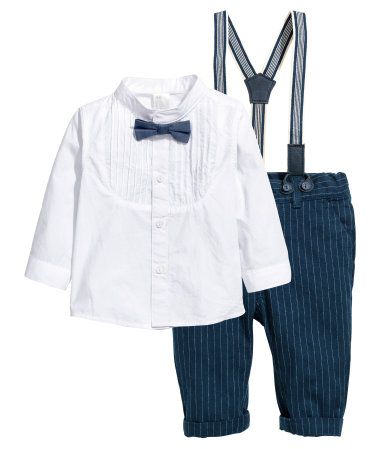 White/dark blue. Set in soft, woven cotton fabric. Collarless shirt with bib front with pin-tucks. Attached bow tie, buttons at front, and cuffs with