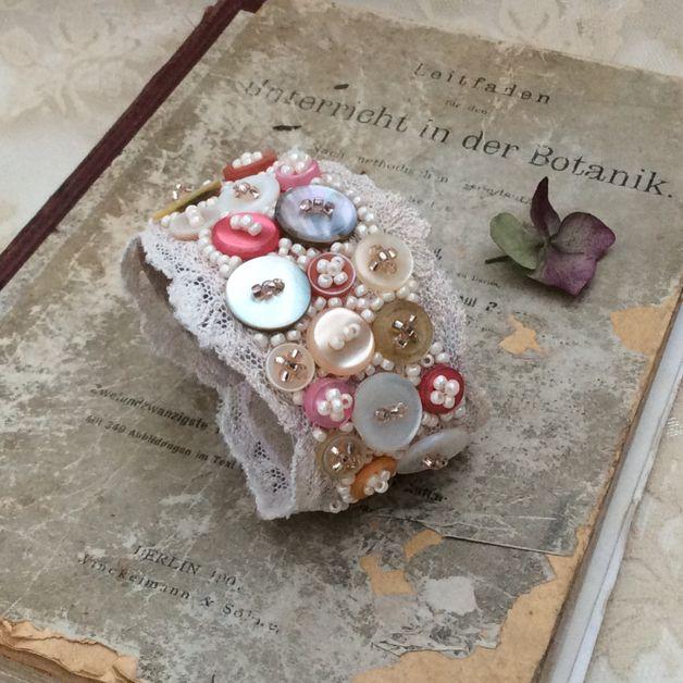 Exklusives Armband bestehend aus antiker, über 100 Jahre alter Spitze, handbestickt mit schimmernden Vintage Knöpfen und hunderten von cremefarbenen Perlen. Das Armband ist mit Wildleder gefüttert...